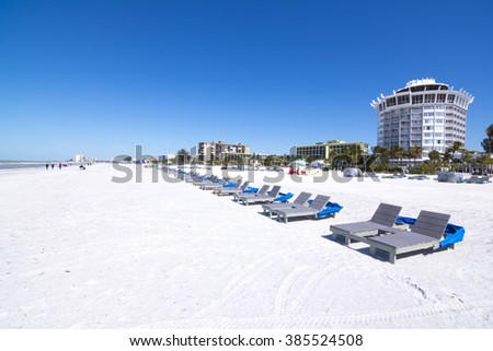 Resort and hotel lounge chairs lined up on clean, white sand under clear, blue sky at beautiful St. Pete Beach in St. Petersburg, Florida - stock photo