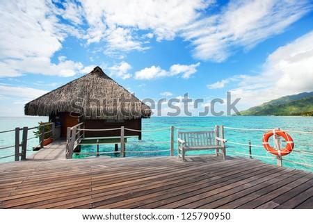 Resort bungalow over tropical water in Tahiti - stock photo
