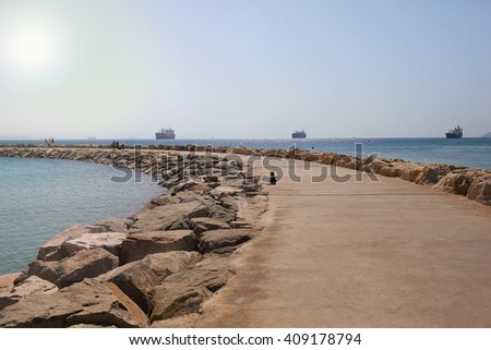 Resort of Eilat. A pier in the sea. on the horizon the ships. The cat sits and looks towards the sea - stock photo