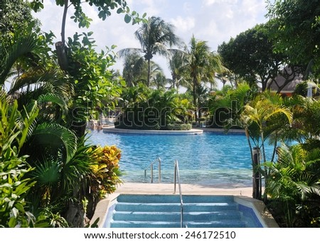 Resort pool. Blue water of the resort pool not only attracts to itself in the hot tropical afternoon, but also is a detail of a beautiful picture.  - stock photo