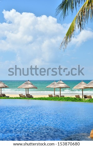 Resort pool with sunbeds near the tropical beach -- tropical vacations - stock photo