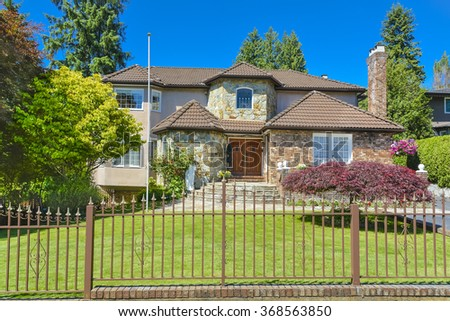 Respectable luxury residential house with metal fence in front in suburb of Vancouver. Beautiful house with green lawn in front on blue sky background. - stock photo