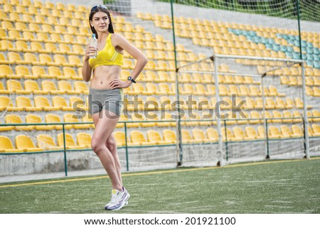 Respite training. Woman in tracksuit holding a water bottle on the football field on a sunny day in sunglasses - stock photo