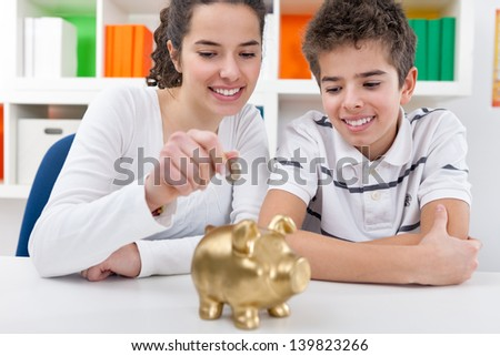 Responsible brother and  sister putting money into piggy bank for future saving