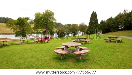 Rest area with many round group tables in a park near a river.