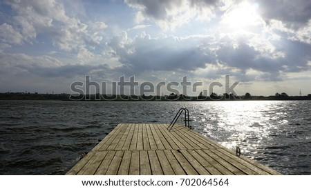 Rest at the lake with silent nature with no people and wooden pier.
