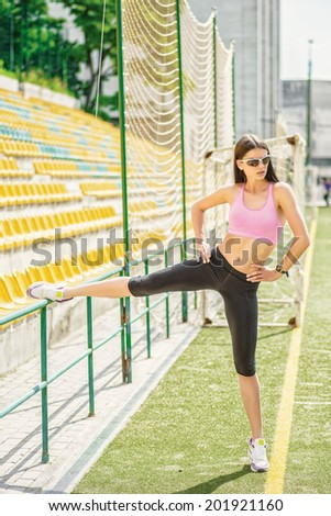 Rest at the training arena. Slim athletic young woman doing workout on the soccer field in sportswear and sunglasses on a sunny hot summer day. - stock photo