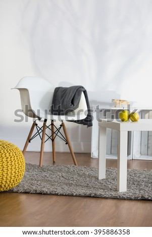Rest corner in modern lounge with white armchair and coffee table - stock photo