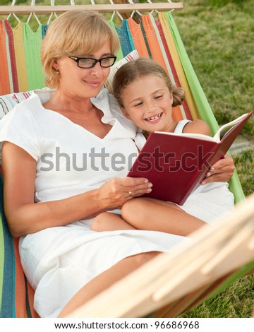 Rest in the garden, happy childhood - girl with mother reading a book in colorful hammock - stock photo