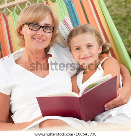 Rest in the garden, parenting - girl with mother reading a book in colorful hammock - stock photo