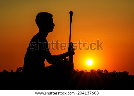 Rest of the sniper with a rifle against the coming sun - stock photo