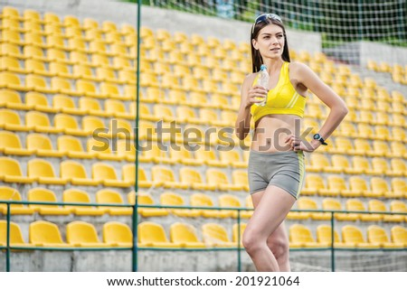 Rest on the field and woman drinking water. Woman in tracksuit holding a water bottle on the football field on a sunny day in sunglasses - stock photo