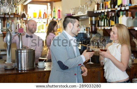 Restaurant adult visitors waiting for table and drinking wine at tavern. Focus on the man - stock photo
