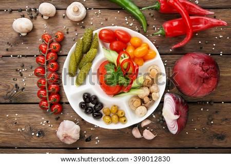 Restaurant appetizer food. Restaurant food assortment plate. Pickled vegetables, tomato, cucumber, pepper, olives platter in restaurant. Catering, served table. Pickled vegetables food plate. Top view - stock photo