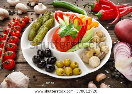 Restaurant appetizer food. Restaurant food assortment plate. Pickled vegetables, tomato, cucumber, peppers, olives platter in restaurant. Catering, served table. Pickled vegetables food plate.  - stock photo