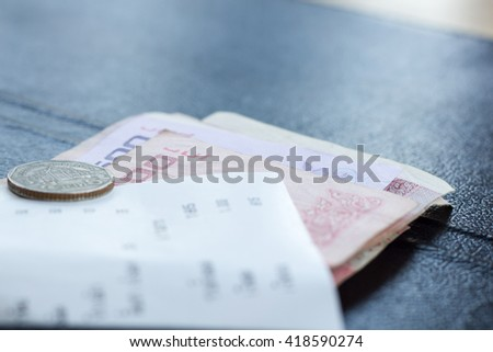 Restaurant bill with money in payment book on the table - stock photo