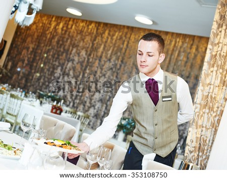 Restaurant catering services. Male waiter with food dish serving banquet table - stock photo