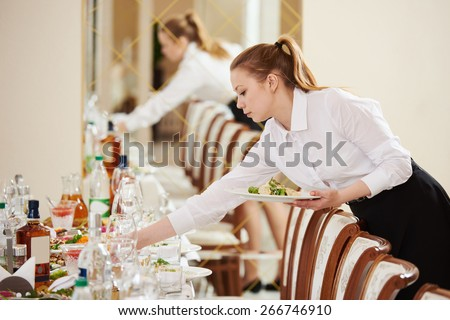 Restaurant catering services. waitress serving banquet table - stock photo