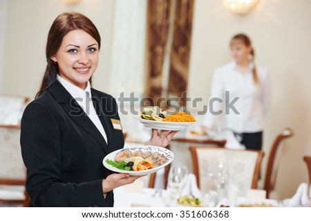 Restaurant catering services. Waitress with food dish serving banquet table - stock photo