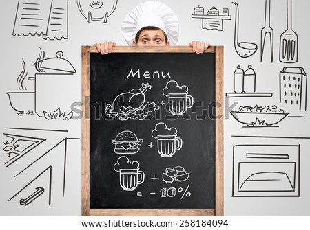 Restaurant chef hiding behind a big chalkboard for a business lunch menu with sketchy notes. - stock photo