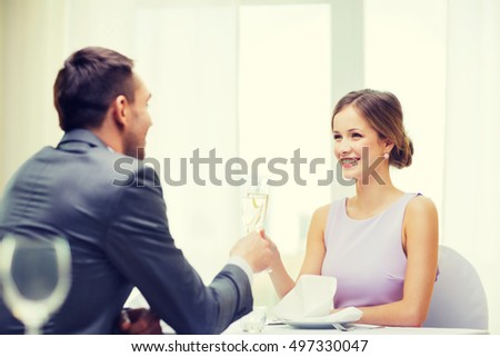 restaurant, couple and holiday concept - smiling woman with glass of champagne looking at husband or boyfriend at restaurant