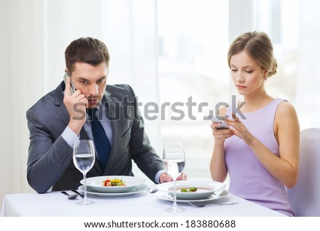 restaurant, couple, technology and holiday concept - busy couple with smartphones at restaurant - stock photo