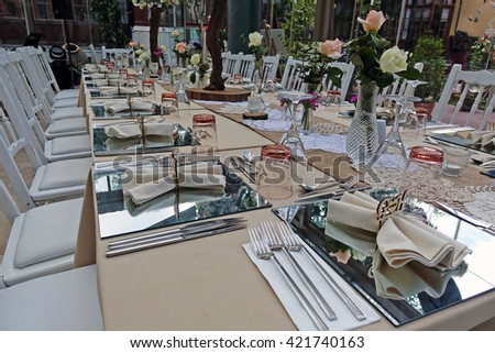 Restaurant.Decorated tables in the restaurant.Image of fine table setting in restaurant.Glasses,dishes,spoons and forks.
