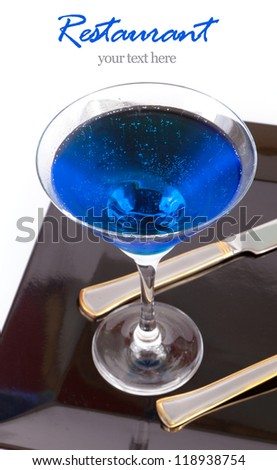 Restaurant Design Blue drink in a cocktail glass in black dish with fork and knife