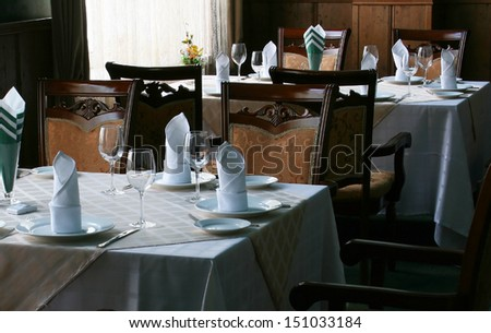 Restaurant dinner table place setting: napkin, wineglass, plate and flowers - stock photo