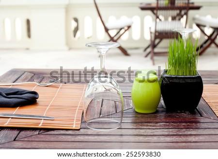Restaurant empty glass setting with fresh green grass in a flowerpot - stock photo