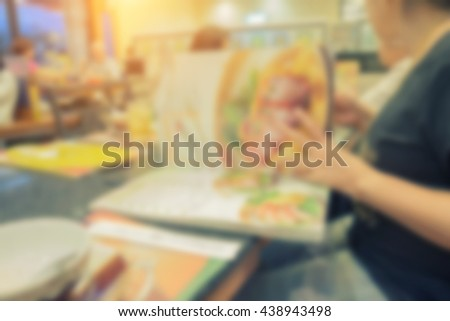 Restaurant, food, eating and holiday concept - close up hand with menu choosing dishes at restaurant - stock photo