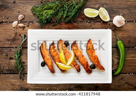 Restaurant food, salmon dish. Hot fish dish. Barbecue grilled fish dish. Restaurant food catering. Salmon barbecue grill top view with lemon and olives. Grilled salmon served in restaurant closeup.  - stock photo