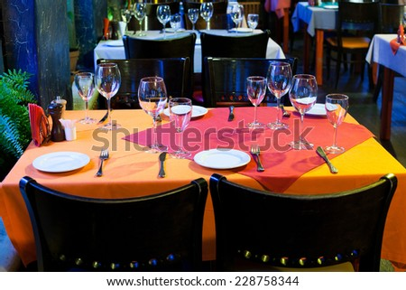 Restaurant hall. Table with red and orange tablecloth, wine glasses, white plates and cutlery. (Soft focus.) - stock photo