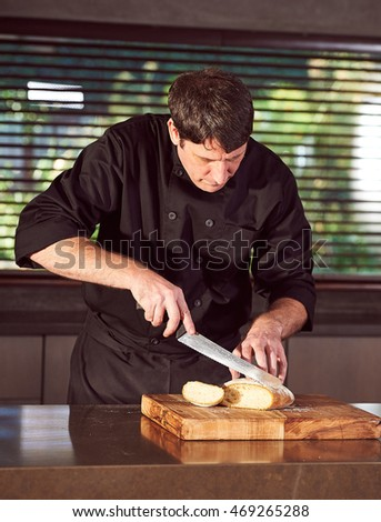 Restaurant hotel private chef slicing fresh loaf of bread