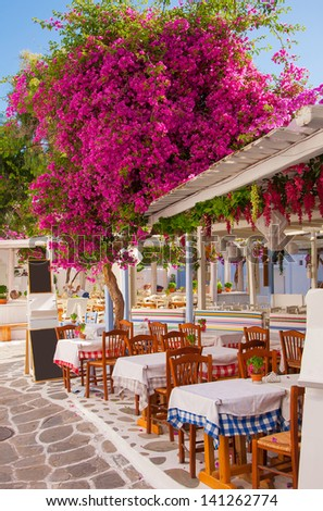 restaurant in the narrow streets of the island town with flowers - stock photo