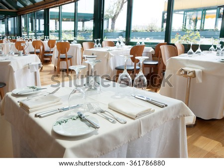 restaurant luxury with beautiful light and with cutlery set in the tables - stock photo