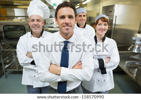 Restaurant manager posing in front of team of chefs smiling at camera - stock photo