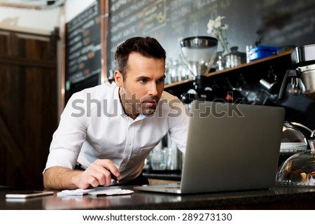 Restaurant manager working on laptop, counting profit - stock photo