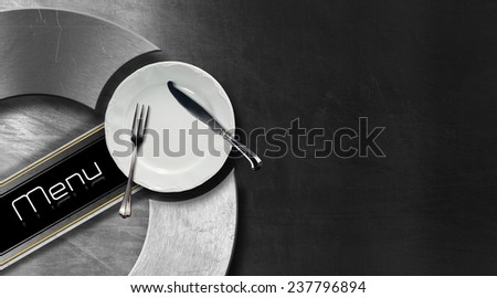 Restaurant Menu Design. Horizontal restaurant menu with empty white plate and cutlery, fork and knife, on black and metal background with metallic circle and diagonal black band - stock photo