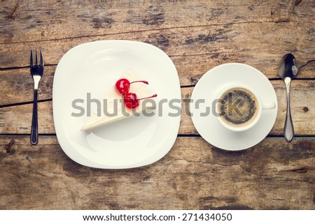 Restaurant menu or recipe background. Toned image top view of breakfast setting with cup of coffee and piece of new york style cheesecake with cherry - stock photo