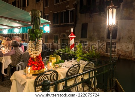 Restaurant on the canal at night in Venice, Italy - stock photo