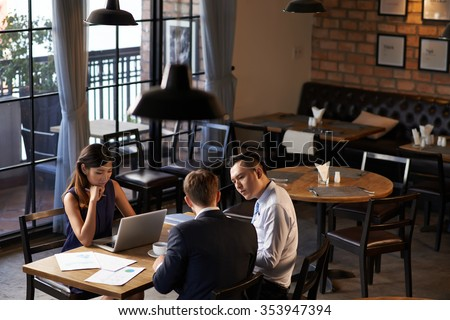 Restaurant owners analyzing earnings at the table - stock photo