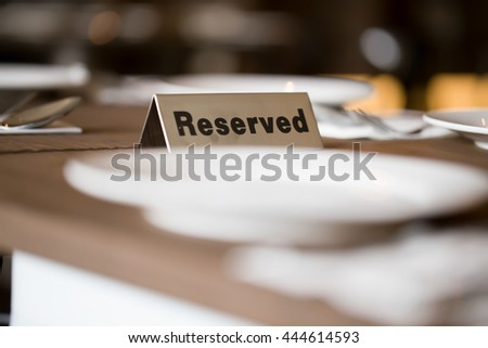 Restaurant reserved table sign with places setting and wine glasses