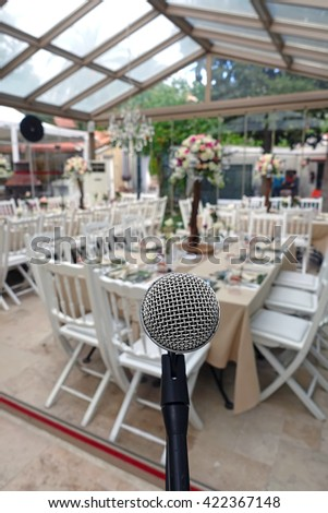 Restaurant.Restaurant ,decorated vith plates, cutlery, glasses, flowers, knives and various decoration materials.The view from stage ,behind the microphone. - stock photo