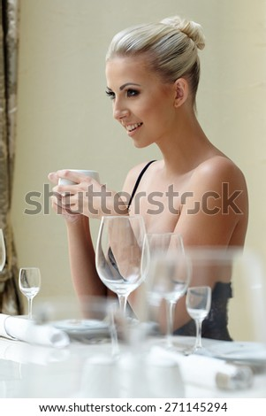 Restaurant. Sexy blonde posing with cup of coffee - stock photo