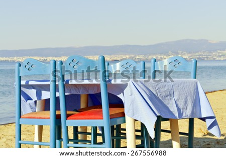 Restaurant table and chairs on the beach for relaxing and romantic dinner - stock photo