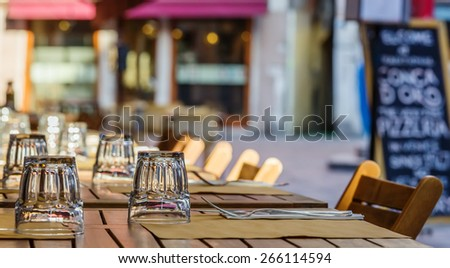 Restaurant table with glasses and menu in the background - stock photo