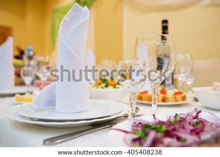 Restaurant table with glasses, napkins and cutlery - stock photo