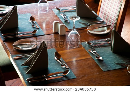 Restaurant table with glasses, plates and dinnerware