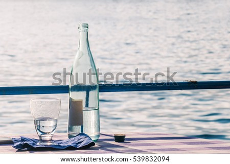 Restaurant table with water bottle and glass near Lake Iseo